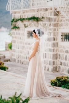 Een vriendelijke bruid in een kanten sluier staat bij een wit bakstenen huis in het oude centrum van perast