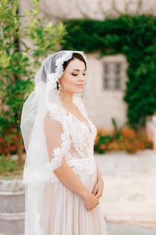 Een vriendelijke bruid in een kanten sluier staat naast een wit huis dat is verstrengeld met een wijnstok in de oude stad