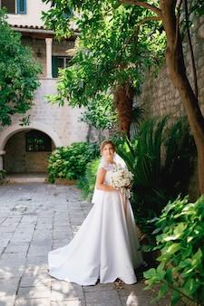 Een vriendelijke bruid staat in een gezellige groene binnenplaats naast een boom en heeft een boeket in haar handen