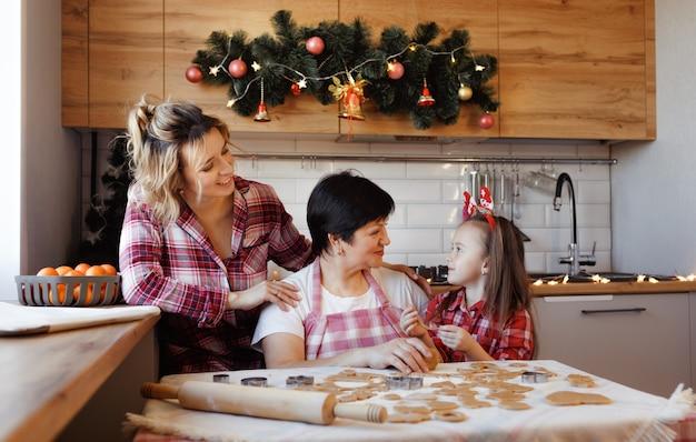 Een vriendelijke familie kookt gemberkoekjes in de keuken en lacht vrolijk