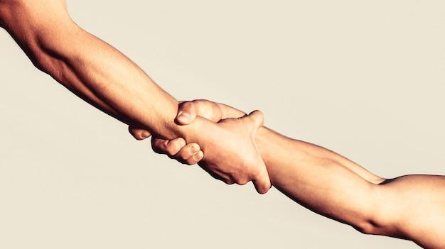 Een vriendelijke handdruk. twee handen, handen schudden. twee handen, helpende arm van een vriend, teamwork. redding, helpend gebaar of handen. sluit omhoog hulphand. helpende hand concept, ondersteuning
