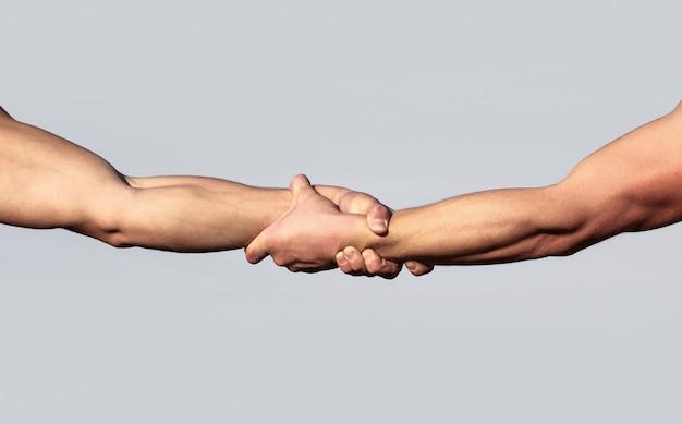 Een vriendelijke handdruk. twee handen, handen schudden. twee handen, helpende arm van een vriend, teamwork. redding, helpend gebaar of handen. sluit omhoog hulphand. helpende hand concept, ondersteuning.