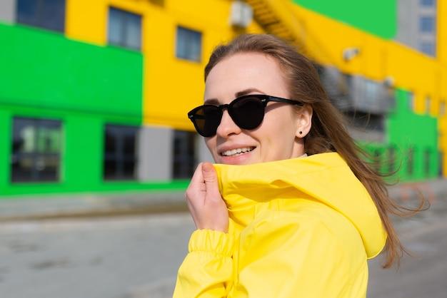 Een vriendelijke jonge vrouw in een gele jas en met een zonnebril op straat