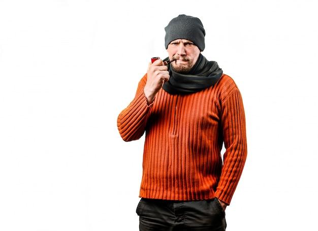 Een vriendelijke man van middelbare leeftijd met een baard, in een gebreide muts, een pijp aan het roken