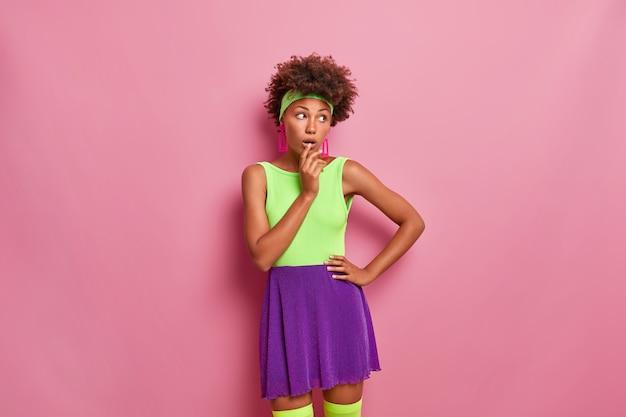 Een vrij donkere jonge vrouw kijkt met verwondering opzij, gekleed in lichte kleren, houdt de mond open, herinnert zich iets ongelooflijks