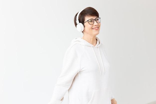 Een vrij enthousiaste vrouw van middelbare leeftijd met een bril en een witte trui luistert naar haar favoriete muziek