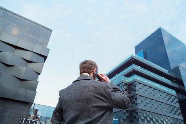 Een vrij geklede mens die op een mobiele telefoon voor een bureauwolkenkrabber spreekt