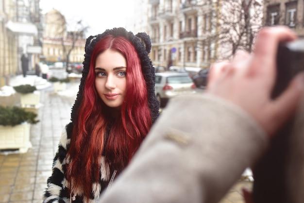 Een vrij informeel meisje met rood haar poseert en kijkt naar de camera terwijl haar vriendin een foto van haar maakt.