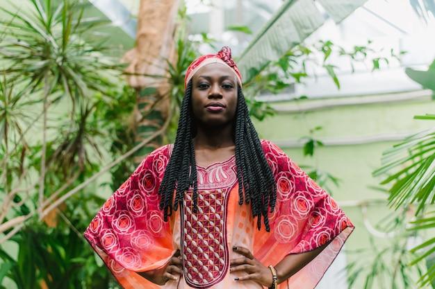 Een vrij jonge afro-amerikaanse vrouw staat onder palmbomen in de jungle en glimlacht breed in een nationaal afrikaans kostuum.