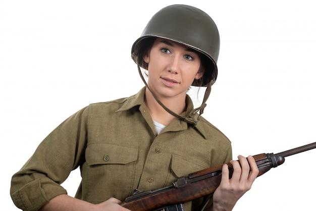 Een vrij jonge vrouw, gekleed in wwii amerikaanse militaire uniform met helm en geweer