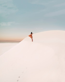 Een vrij jonge vrouwelijke reiziger die van het leven in de woestijn geniet. deze artistieke foto is gemaakt in de duinen met een prachtige zonsondergang als achtergrond. het meisje draagt een jurk die beweegt door de wind.