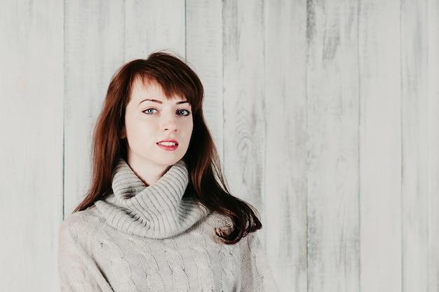 Een vrij langharig meisje in een grijze trui, glimlachend, lichte achtergrond