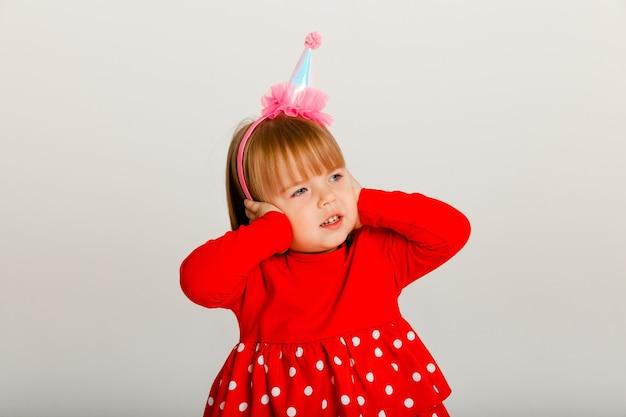 Een vrolijk 4-jarig meisje met een feestelijke hoed en een rode trui viert haar verjaardag. fluitje op witte achtergrond