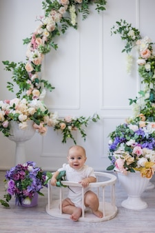 Een vrolijk babymeisje in een witte bodysuit zit in een arena op een achtergrond met bloemen