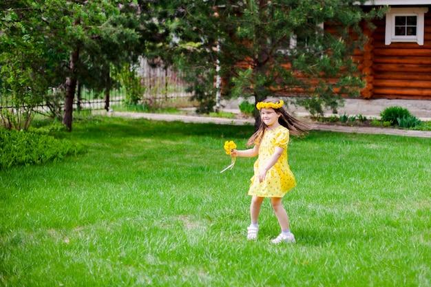 Een vrolijk blank meisje in een gele jurk danst en draait om zich heen een meisje met een krans en...