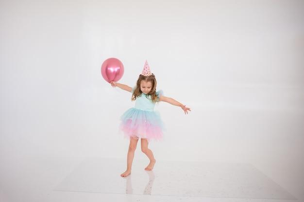Een vrolijk blond meisje in een elegante jurk staat met een roze ballon op een witte achtergrond met een plek voor tekst