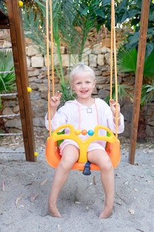 Een vrolijk en vrolijk kindmeisje zwaait in de zomer op een schommel op een houten platform en glimlacht