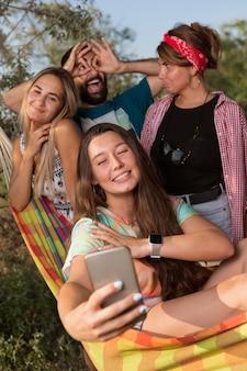 Een vrolijk gezelschap van jonge mensen, vier mensen, in een hangmat, maakt een selfie ter herinnering, zomervakantie