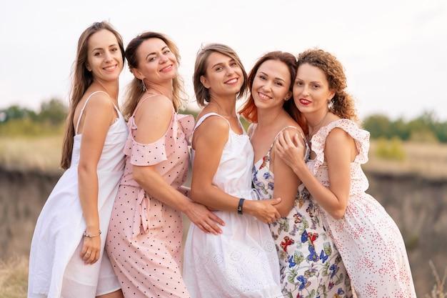 Een vrolijk gezelschap van mooie vriendinnen geniet van het gezelschap en heeft samen plezier op een pittoreske plek met groene heuvels.