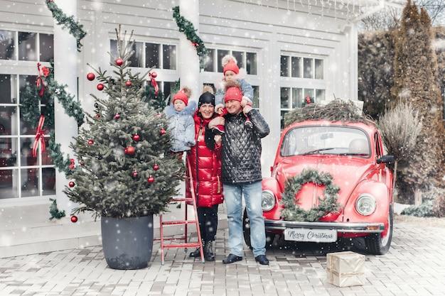 Een vrolijk gezin van vier staat naast een rode auto en heeft veel plezier