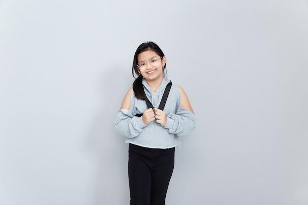 Een vrolijk glimlachend aziatisch meisje draagt een schooltas