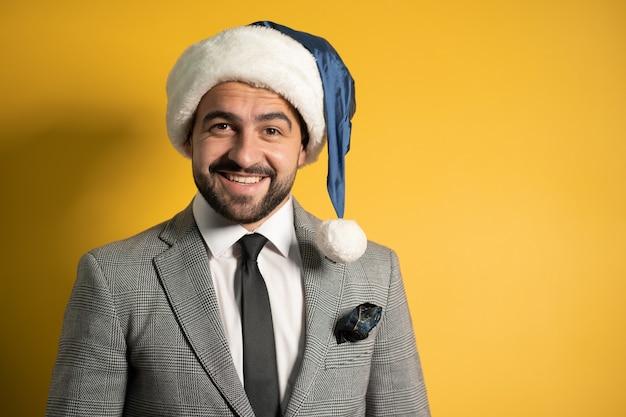 Een vrolijk glimlachende medewerker of flight manager zet een kerstmuts op en staat klaar om de medewerkers te feliciteren. knappe lachende bebaarde man in kerstmuts geïsoleerd op gele achtergrond.