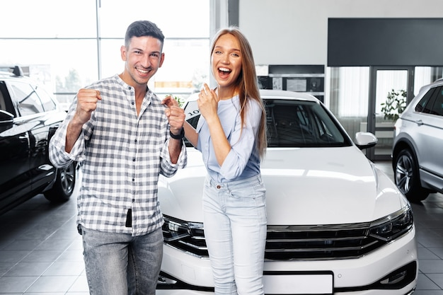 Een vrolijk jong stel dat bij de dealer een nieuwe auto koopt