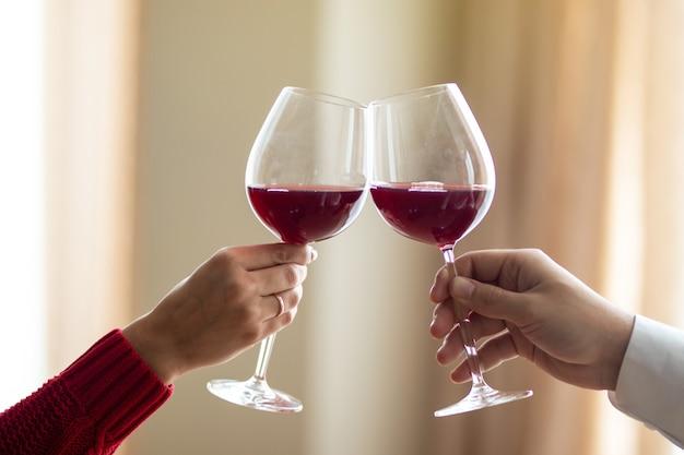Een vrolijk jong stel dat hun wijnglazen kruist in een restaurant. een man en zijn vriendin die wijn drinken in een café. rode roos op een tafel. valentijnsdag concept.