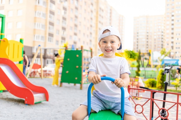Een vrolijk jongetje op een schommel in de speeltuin