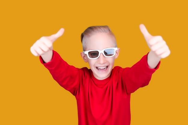 Een vrolijk kind in rode kleren en een bril toont een duim omhoog op een gele achtergrond