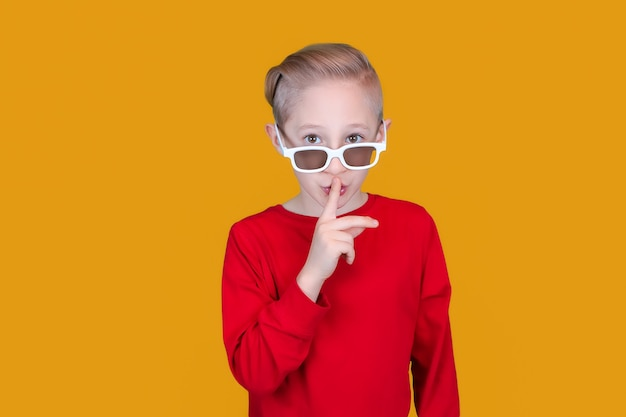 Een vrolijk kind met een 3d-bril voor kinderen legt zijn wijsvinger tegen zijn lippen en maakt een stil gebaar