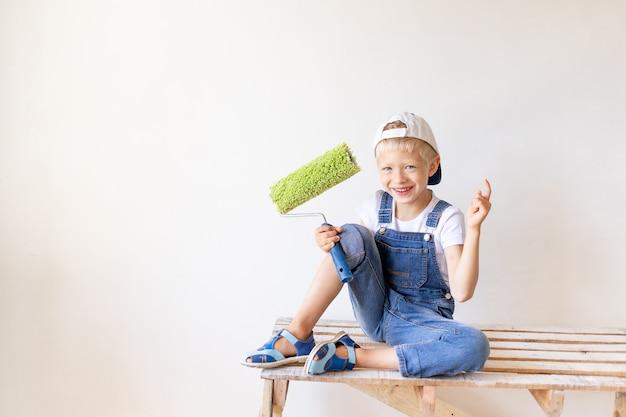 Een vrolijk kind zit op een bouwladder in een appartement met witte muren en een rol