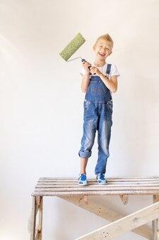 Een vrolijk kind zit op een bouwladder in een appartement met witte muren en een roller in zijn handen en toont een duim omhoog, een plek voor tekst, het concept van reparatie