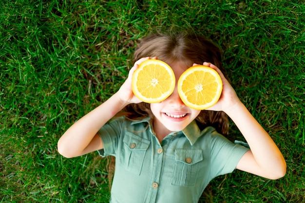 Een vrolijk kindmeisje in de zomer op het gazon bedekte haar gezicht met sinaasappels op het groene gras, heeft plezier en verheugt zich, ruimte voor tekst