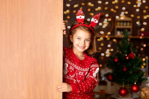 Een vrolijk kindmeisje kijkt uit achter de deur in een donkere keuken met een kerstboom voor nieuwjaar of kerstmis, glimlachend en lachend in een kerstmanhoed, ruimte voor tekst