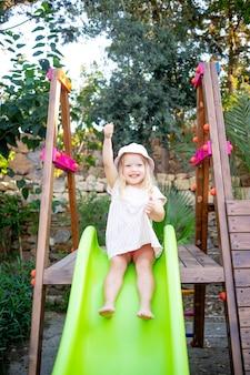 Een vrolijk kindmeisje rijdt van een glijbaan op de speelplaats en lacht in de zomer in een panamahoed en blote voeten