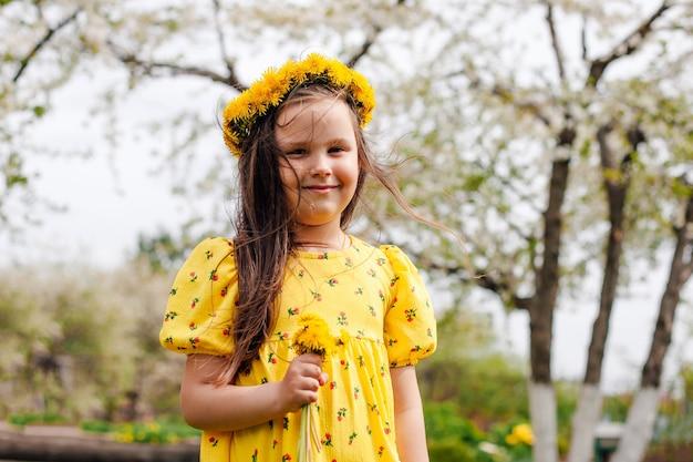 Een vrolijk lachend meisje met haar dat in de wind vliegt met een krans van gele paardebloemen op haar hoofd