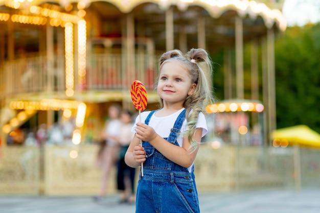 Een vrolijk meisje in een pretpark op de achtergrond van een carrousel eet een grote lolly