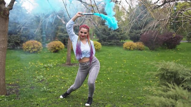 Een vrolijk meisje in een shirt en spijkerbroek met heldere regenboogvlechten en ongewone make-up. ze danst zich verstoppen in dikke blauwe kunstmatige rook