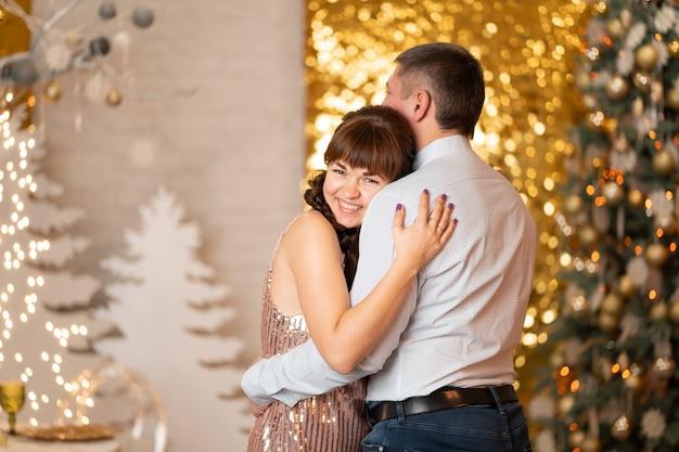 Een vrolijk meisje knuffelt een man tussen sparkles en gerlands op een kerstfeest.