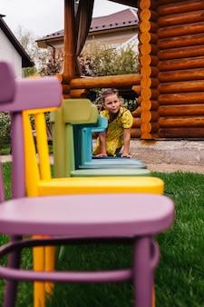Een vrolijk meisje kruipt langs een rij kleurrijke houten stoelen een meisje vermaakt zich in de achtertuin