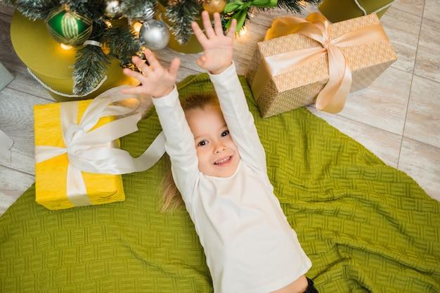 Een vrolijk meisje ligt op een groene gebreide deken onder de kerstboom met cadeautjes en hief haar handen op