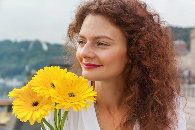 Een vrolijk meisje loopt door de stad met een boeket gele gerberbloemen