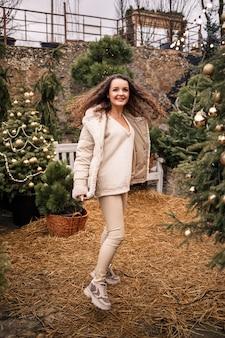 Een vrolijk meisje loopt tussen de bomen en lacht, ze heeft een nieuwjaarsstemming