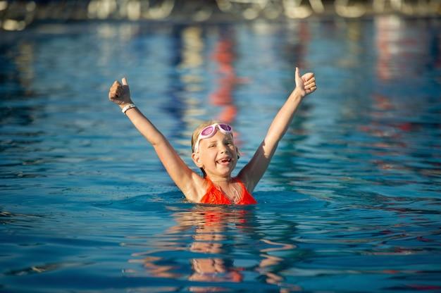 Een vrolijk meisje met opgeheven handen speelt in het zwembad. zomervakantie in het waterpark, reizen.