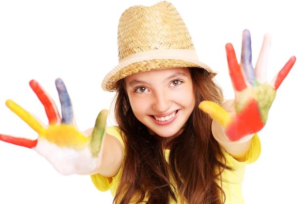 Een vrolijk meisje met verf op haar handen