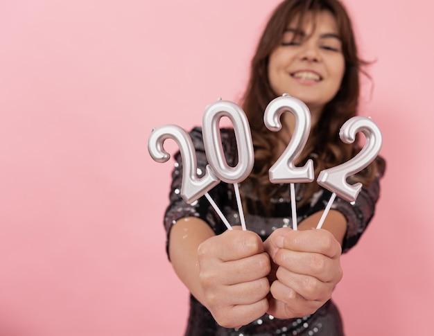 Een vrolijk meisje op een roze achtergrond houdt de cijfers in haar handen