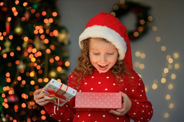 Een vrolijk meisje opende een nieuwjaarscadeau en was verrast