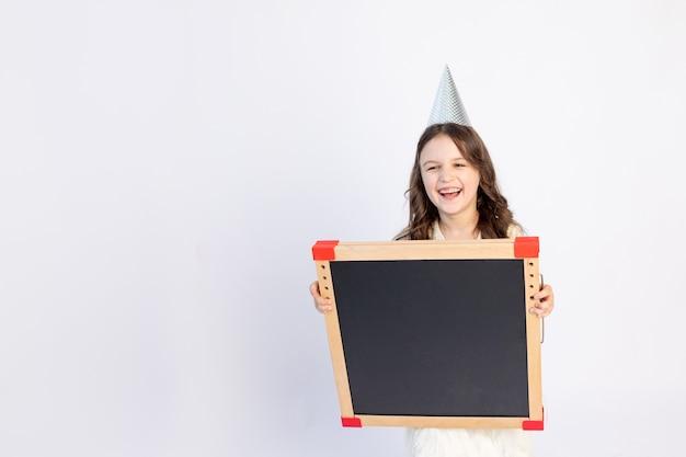 Een vrolijk meisje staat op een witte achtergrond geïsoleerd in een pet en een nette jurk en heeft een zwart bord voor het tekenen van een plek voor tekst.