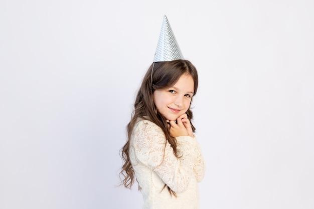Een vrolijk meisje staat op een witte geïsoleerde achtergrond in een pet en een nette jurk met haar handen ineengevouwen, een wens doen, een plek voor tekst, een vakantieconcept